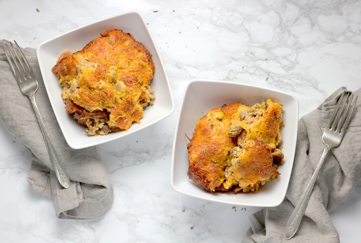 two plates of bacon cheeseburger casserole next two each other with a fork beside each dish