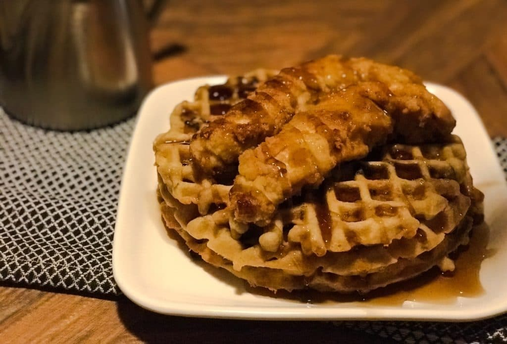 chicken and waffles served on a plate with drizzled syrup over dish