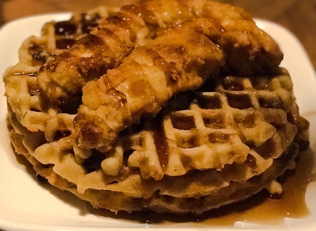 three waffles stacked with two chicken tenders on top