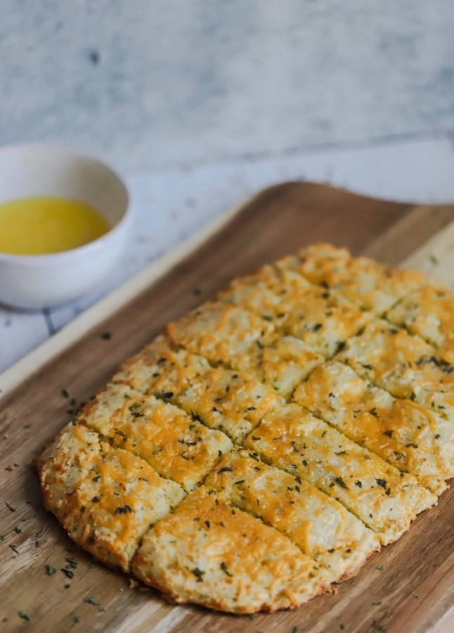 keto garlic bread on a wooden plate cut into pieces with a bowl of butter next to it