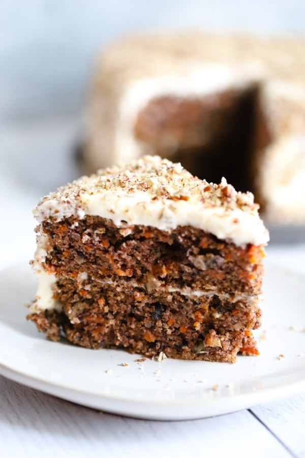 a close up of a slice of carrot cake from the side with the rest of the cake in the background