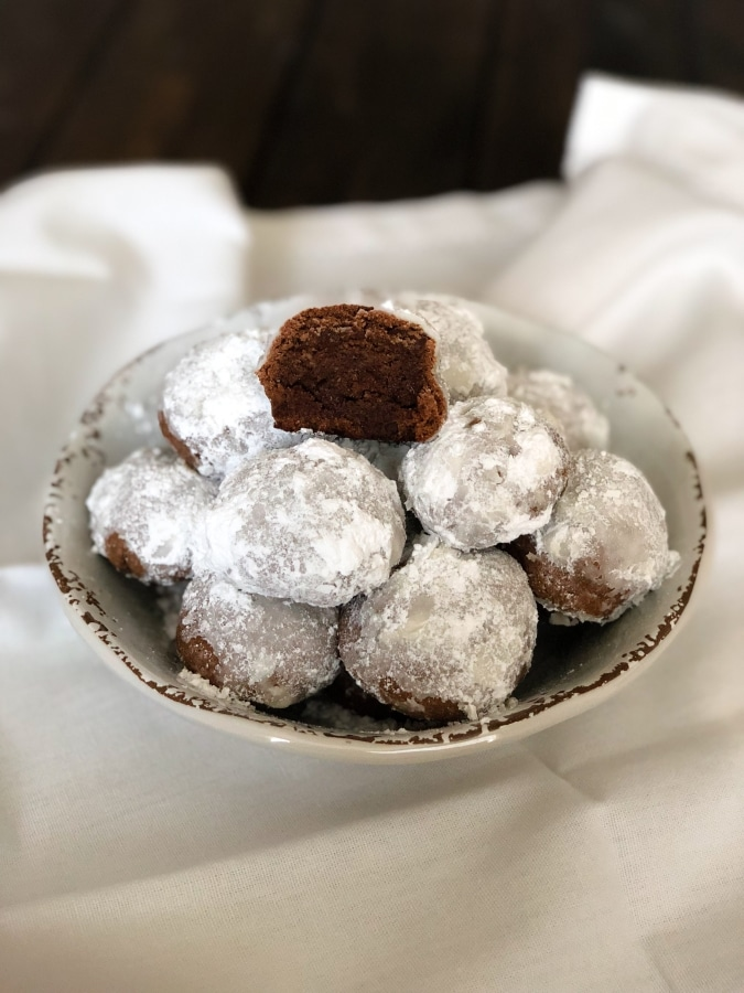 a bowl of snowball cookies with one snowball taken a bite