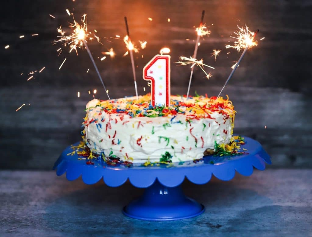 keto birthday cake lit up with a number one candle and four sparklers going off