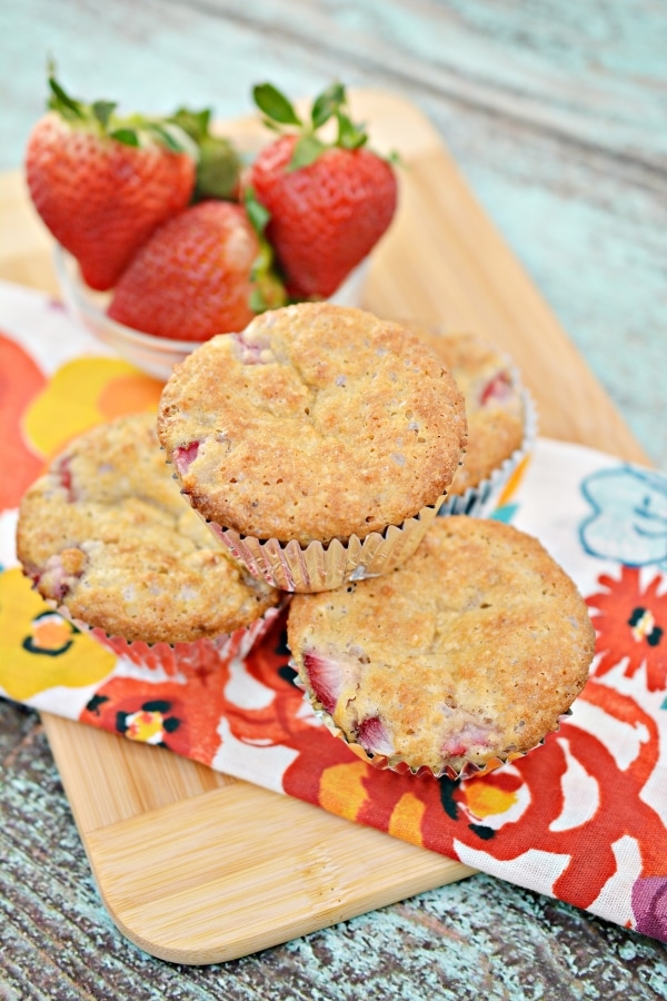 Three keto strawberry muffins on a cutting board with one muffins on top. Bowl of strawberries in the background.