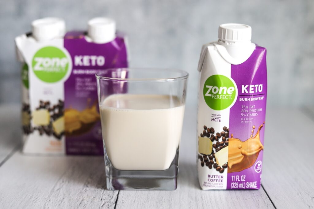 photo of a glass of ZonePerfect butter coffee keto shake with the package next to it and box behind the glass