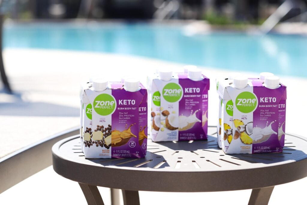 three ZonePerfect keto shake packages on top of a pool end table with the pool in the background