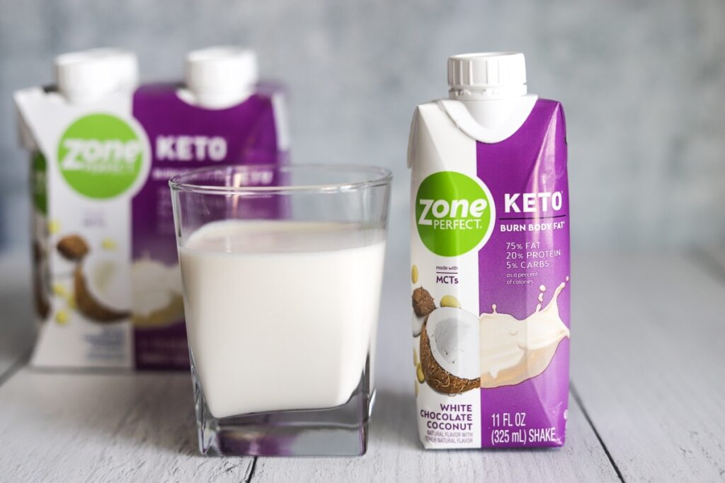 photo of a glass of ZonePerfect white chocolate coconut keto shake with the package next to it and box behind the glass