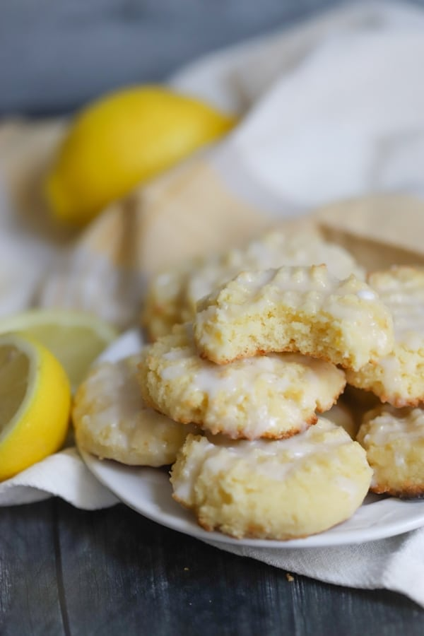 a plate of keto lemon cookies with a bite taken out of the one on top
