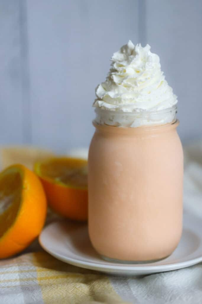 orange creamsicle ice cream in a mason jar with whipped cream on top and two orange on the side