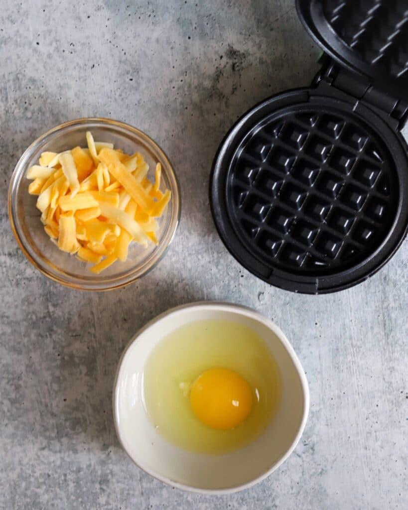 top view of a bowl of cheese, a bowl with an egg, and a mini waffle maker on the side