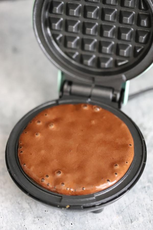 poured batter beginning to cook on waffle skillet