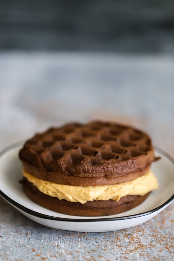 A centered peanut butter cup chaffle sitting a top of a plate