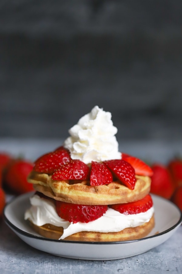 strawberry shortcake chaffle in the center on top of a plate with a few strawberries blurred in the background behind