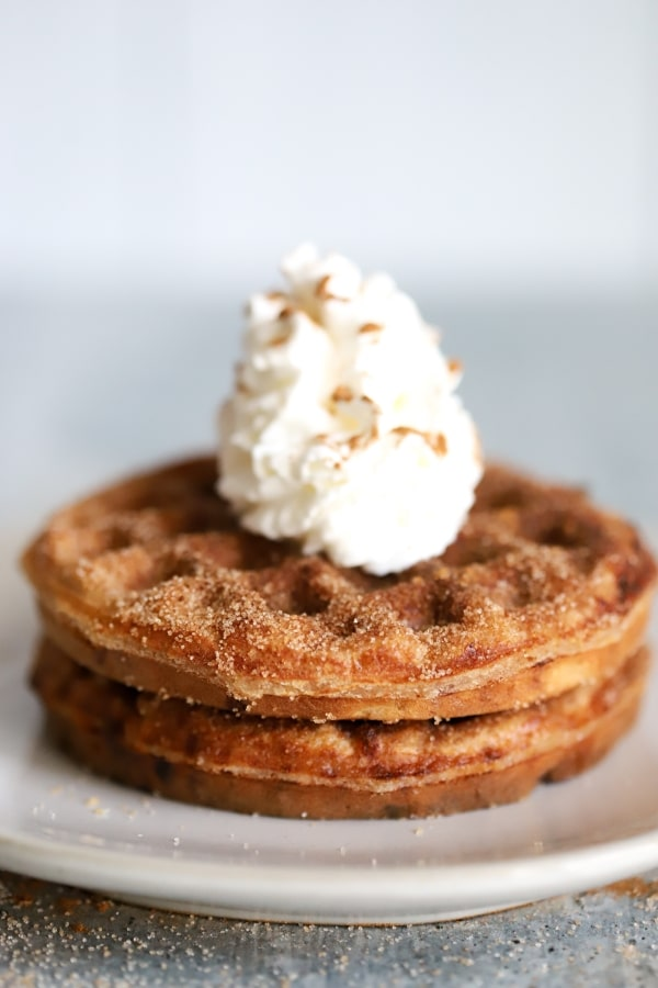 two keto snickerdoodle chaffles stacked on a plate in the center with whipped cream on top