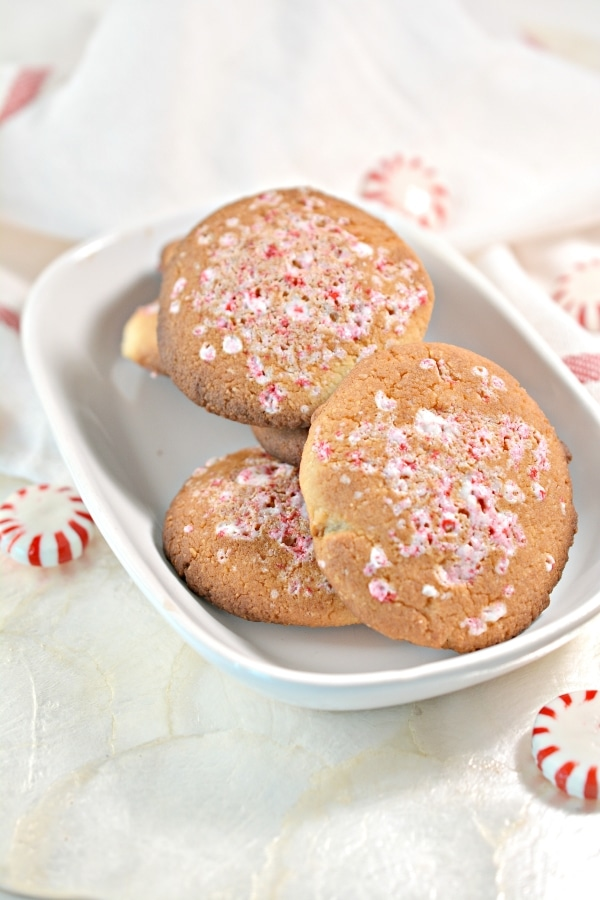 keto peppermint cookies in a ceramic bowl with peppermint candies surrounding on the table