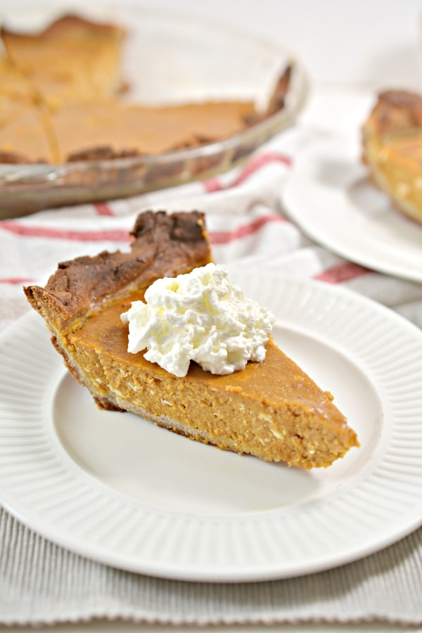 a slice of pumpkin pie on a plate with the rest in the background