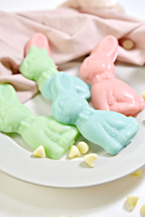 plate of keto chocolate easter bunnies with white chocolate chips scattered on a plate