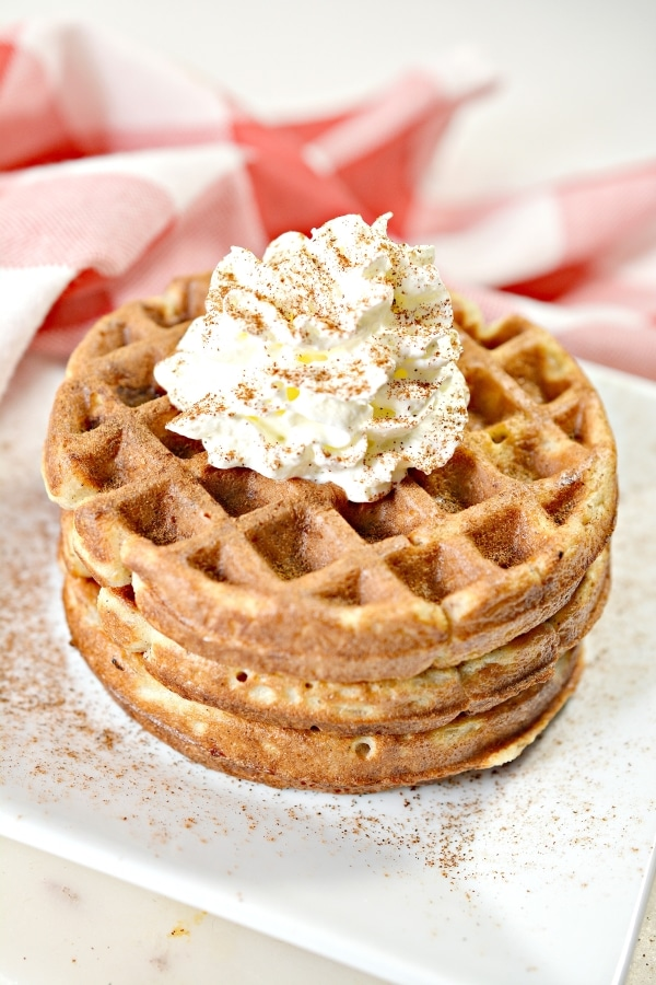 stack of apple pie chaffles on a plate with whipped cream on top