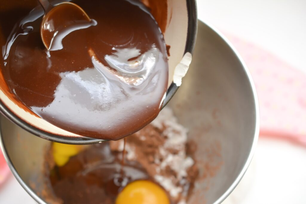 pouring melted chocolate mixture in a bowl