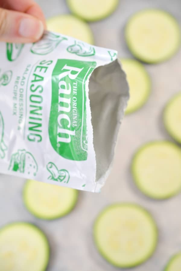 pouring ranch seasoning over zucchini slices