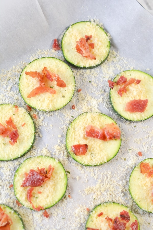 parmesan cheese getting added to zucchini slices on a sheet pan