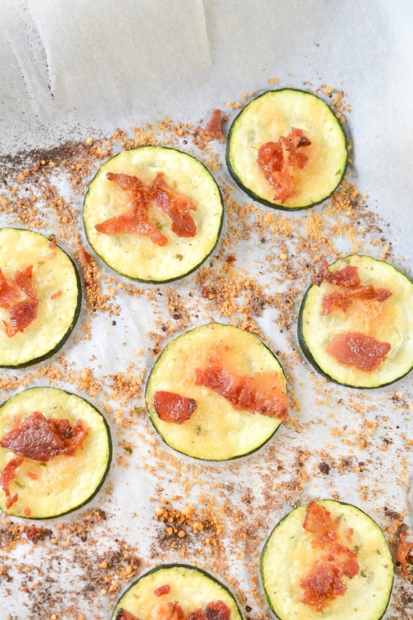 top view of cooked zucchini slices on a baking sheet pan