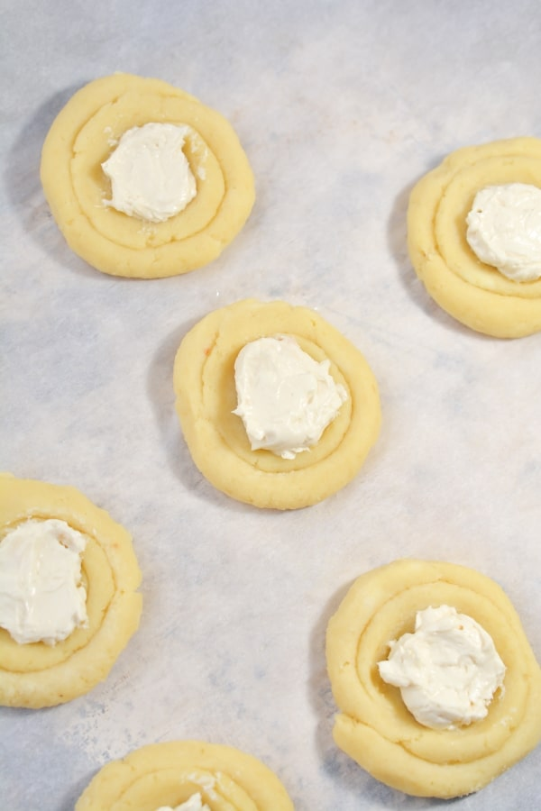 cream cheese added onto of danish dough on parchment paper