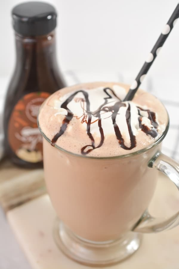 keto chocolate coffee milkshake in a glass cup with choczero bottle in the background